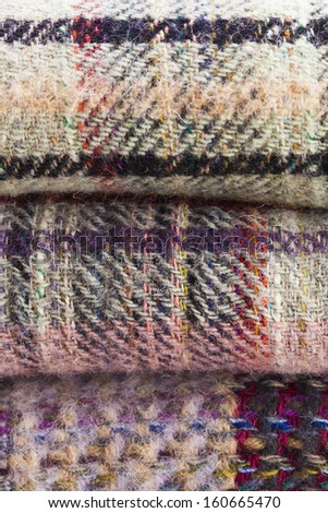 Stacked and folded picnic blankets with woven checked multicolored pattern