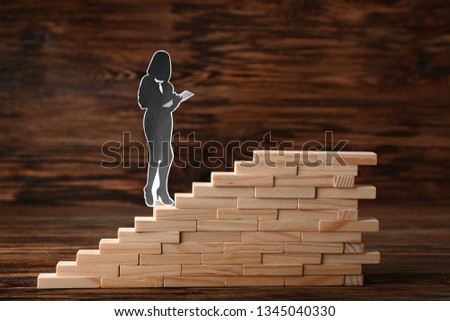 Stacked blocks with human figure on wooden background. Concept of career #1345040330