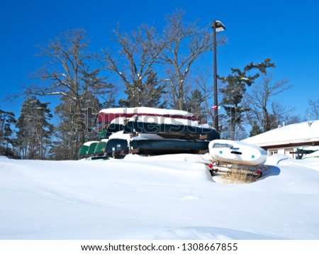 Stacked canoes and a sail boat covered in snow in Minnesota winter scene with space for copy.