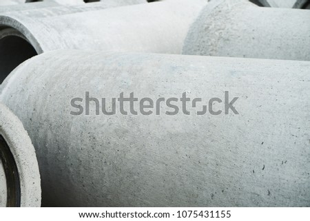 Stacked cement pipes at concrete factory, outdoors warehouse . Industrial production of cement products. Industry manufacturing concept #1075431155