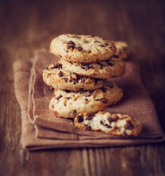 Stacked chocolate chip cookies on brown napkin. Symbolic image. Concept for a tasty snack. Sweet dessert. Rustic wooden background. Selective focus. Close up.