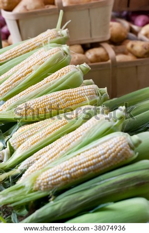 Stacked cobs of corn piled for display at a local outdoor farmers market, with baskets of potatoes in the background.
