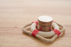 Stacked coins in red lifebuoy or lifebelt with wooden background copy space. Assets wealth, money saving or money investment protection and security by insurance concept. Risk management analysis.