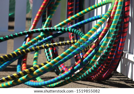 Stacked colourful hula hoop being used at a street fair to entertain children and adults #1519855082
