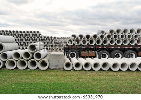 Stacked concrete pipes and loaded flatbed trailer