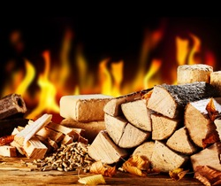 Stacked dried logs in front of a burning fire on a cold autumn night with wood pellets and bricks