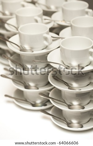 Stacked empty teacups with teaspoons at a function over white background