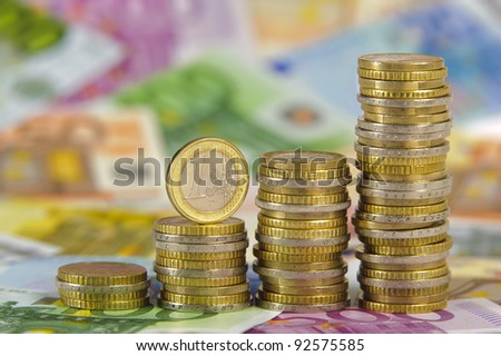 stacked euro coins on banknotes