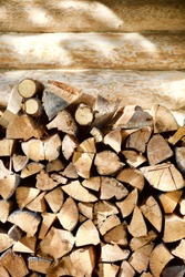 Stacked firewood near the wall of a log village house close-up. Firewood storage close up. Stocks of wooden logs close-up. Chopped wood and sun glare. Logging in the village. Woodpile with firewood
