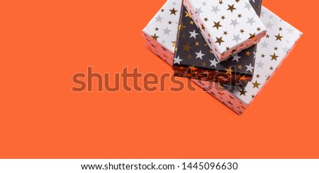 Stacked gift boxes with golden stars on orange background. Giving presents concept.