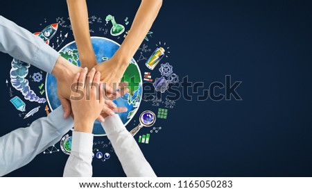 Stacked hands with creative globe and business sketch. Worldwide teamwork and plan concept  #1165050283