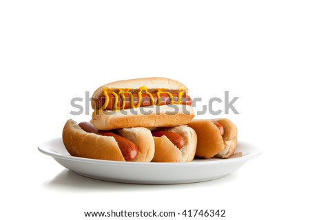 Stacked hot dogs with mustard and buns on a plate and a  white background