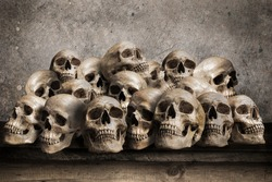 Stacked human skulls on old wooden table in front of grunge concrete wall