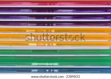 Stacked jewel cases of various colors provide a linear pattern of color and parallel lines. - stock photo