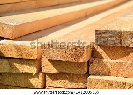 Stacked lumber. Folded wood.Closeup wooden boards.The surface of the end of the board.Lots of planks stacked on top of each other in the warehouse.Lumber for use in construction. Foto stock ©