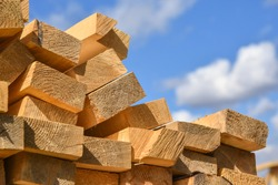 Stacked lumber on blue sky.Folded wood.Closeup wooden boards.The surface of the end of the board.Lots of planks stacked on top of each other in the warehouse.Lumber for use in construction.