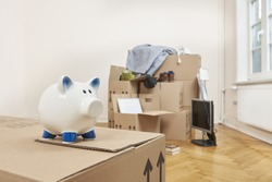 Stacked moving cartons are in an apartment. in the foreground is a white piggy bank - save with a building society