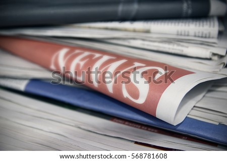 Stacked newspapers. On one in bold font word news is showing