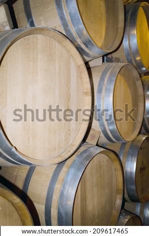 Stacked oak barrels in a winery. Winemaking industry