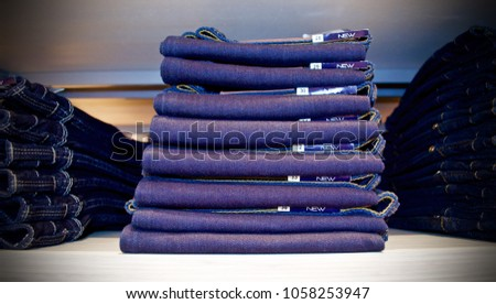 Stacked of folded jeans in store on wooden shelf. #1058253947