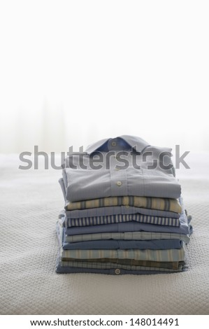 Stacked of ironed and folded shirts on bed