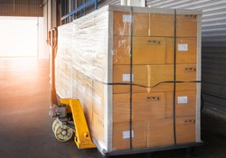 Stacked of Package Boxes Wrapped Plastic Flim on Pallet with Hand Pallet Truck. L-Shape Pallet Corrugated Paper Cardboard Angle Corner Edge Protector. Shipment Boxes. Warehouse Logistics.