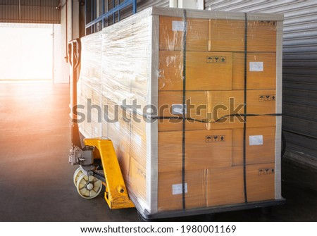 Stacked of Package Boxes Wrapped Plastic Flim on Pallet with Hand Pallet Truck. L-Shape Pallet Corrugated Paper Cardboard Angle Corner Edge Protector. Shipment Boxes. Warehouse Logistics. Stock fotó ©