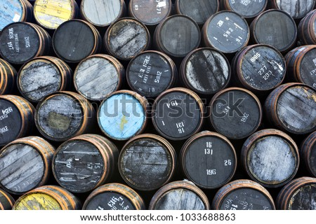Stacked pile of old wooden barrels and casks at whisky distillery in Scotland. #1033688863