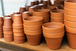 Stacked red clay pots for planting at sale in a garden center