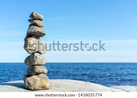 Stacked Rocks balancing, stacking with precision. Stone tower on the shore. Copy space. #1458035774
