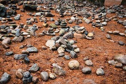 Stacked rocks/pebbles on a bed of pine needles fallen after autumn. A large group of rock found around it.