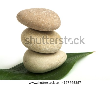 Stacked stones on base of green leafs. White isolated studio shot.