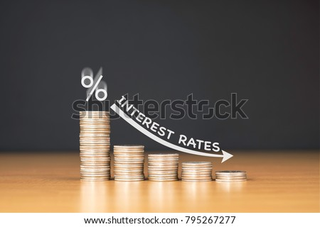 STACKED US QUARTER COINS ON WOODEN TABLE WITH WHITE ILLUSTRATION SHOWS DECREASING OF INTEREST RATES / FINANCIAL CONCEPT ストックフォト ©