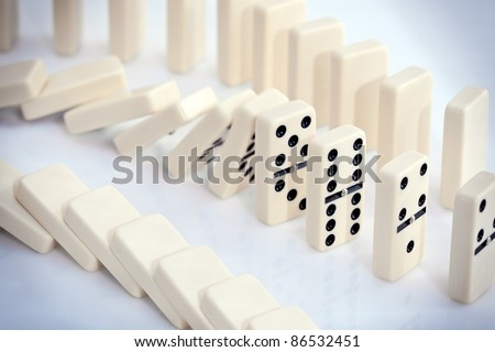 Stacked white dominoes falling over.