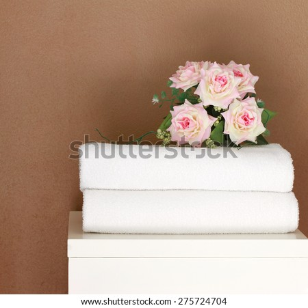 Stacked white spa cloth beach towels with brown background.