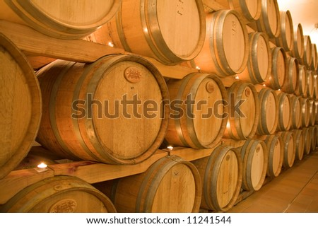 stacked win barrels in the wine cellar