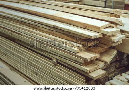 Stacked wooden bars fence on a lumber yard. Building materials. #793412038