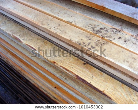 Stacked wooden boards and planks in shed close up #1010453302