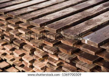 Stacked wooden planks pavement used outside for covering sandy surface for convenient walking.