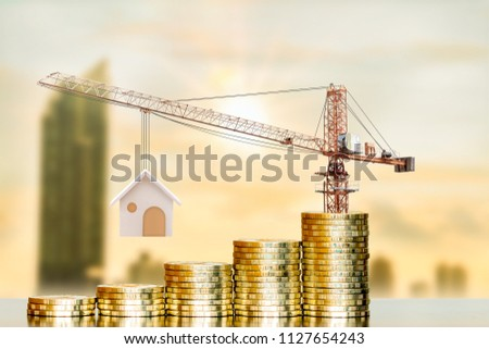 Stacking gold coin with increase and tower crane and hoist brake solutions with build new house on photo blur cityscape background, saving money and loan for construction real estate and home concept.