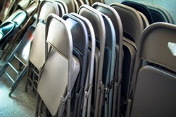 Stacks and Rows of Metal Steel Iron Collapsible Fold Up Folding Chairs o Different Colors leaning up against a Brick Cinder Block Wall in a Storage Room