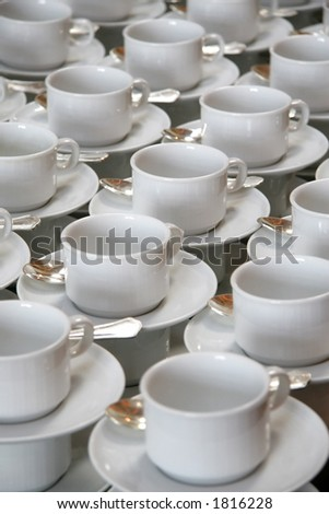 Stacks of coffee cups on saucers with silver teaspoons