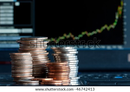 Stacks of coins  and a up trend chart as the background