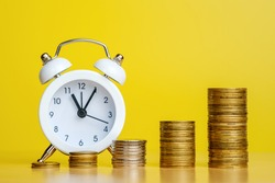 Stacks of coins in row ascending and alarm clock. time is money, efficient business, great income in short time concepts. Copy space for text