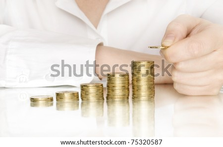 stacks of coins like diagram with reflection and hand put coin