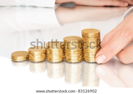 stacks of coins like diagram with reflection and hand put coins