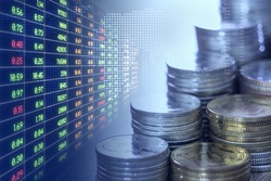Stacks of coins money and stock trading board in blue with digital world map on background