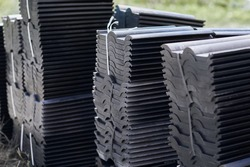Stacks of dark modern roof tiles for covering the house. Tiles are stacked in standard packaging ready for transportation