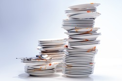 Stacks of dirty dishes, isolated on white.