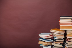 stacks of educational books against the background of the wall in the library